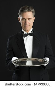 Mature waiter in tuxedo looking at serving tray isolated over black background