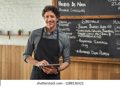 Mature waiter wearing black apron and standing in front of the blackboard with the menu of the day. Portrait of smiling man holding digital tablet and looking at camera. Happy small business owner.