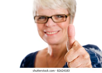 Mature, white haired woman with glasses with a thumb up.