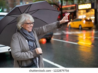 Mature white haired woman hailing taxi cab on New York city stre