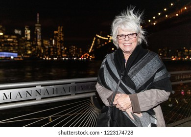 Mature white haired woman outside enjoying view of Manhattan New York at night