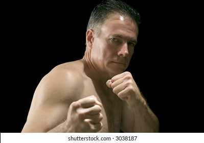 Mature, white, male with his hands made into fists and his arms raised as if ready to defend himself, picture isolated on black.