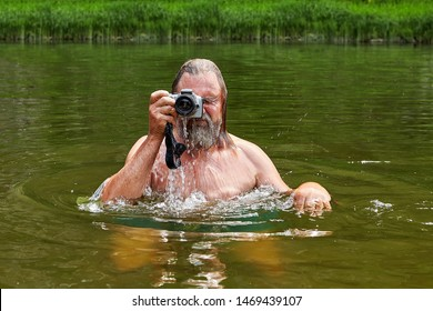 Mature white man about 50 years old with beard is taking photos by waterproof camera being in river's water.