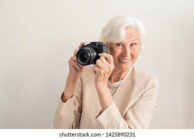 Mature white-haired smiling female photographer with photocamera by face standing on light background