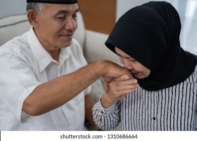 mature wife with hijab shake and kiss her husband's hand at home