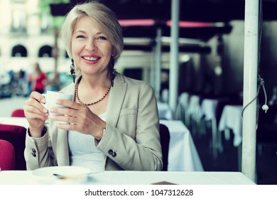 Mature woman 50s years old is lunching with coffee in cafe.