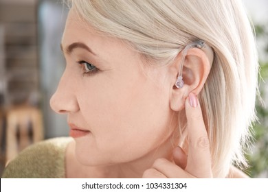 Mature woman adjusting hearing aid indoors