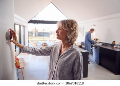 Mature Woman Adjusting Wall Mounted Digital Central Heating Thermostat Control At Home