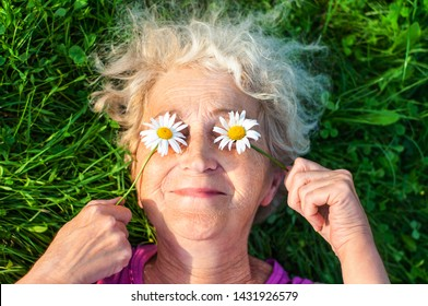 Mature woman after 60 is lying on the lawn holding chamomile eyes. Care for women's wrinkled skin. Vision and eye care. Women Health