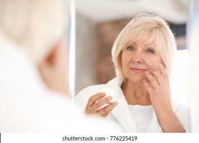 Mature woman applying anti-aging cream at home