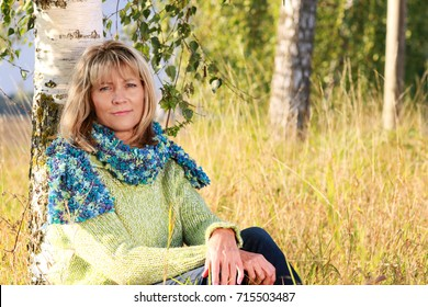 Mature woman in autumn with pullover sitting in a meadow leaning against a birch tree