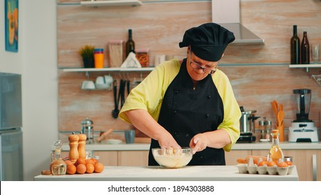 Mature woman baker mixing by hand cracked eggs with flour in home kitchen following traditional recipe. Retired elderly chef with bonete kneading in glass bowl pastry ingredients baking homemade cake