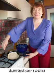 Mature woman bakes pancakes at her kitchen