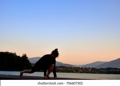 Mature woman in black clothes doing yoga on a wood jetty on Faaker See in Austria, early in the morning at sunrise