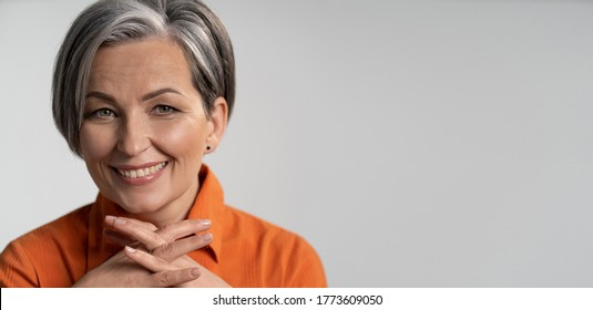 Mature woman broadly smiling with fingers crossed. Happy female model in orange shirt. Close up portrait. Maturity concept. Horizontal template with empty place at right side.