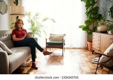 Mature woman browsing the internet with a digital tablet while sitting alone on a sofa in her sunny home