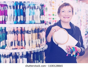 Mature woman buying mouline, cross-stitch canvas and embroidery hoops for her hobby