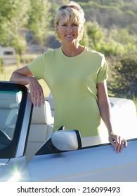 Mature woman by convertible car, smiling, portrait