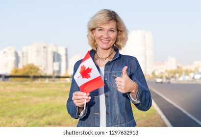 Mature woman with canada flag showing thumb up standing against city and blue sky.