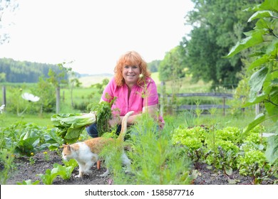 Mature woman and cat in garden, portrait