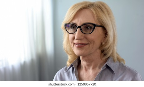 Mature woman choosing eye glasses in oculist cabinet, health problems in old age