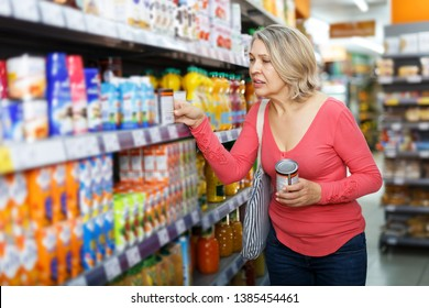 mature woman choosing food products on shelves in grocery shop