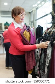 Mature woman choosing   purchase in clothing store.