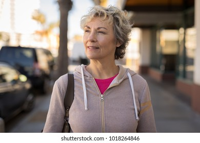 Mature woman in city walking street serious face