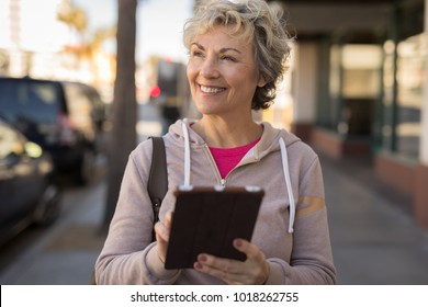 Mature woman in city walking using tablet computer