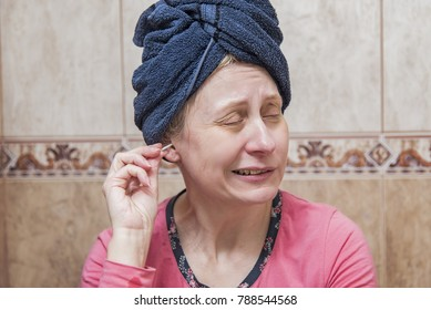 Mature woman cleaning her ears with an ear brush, or a cotton swab, not really enjoying the process