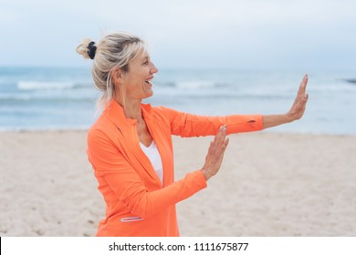 Mature woman in a colorful orange top standing on a beach with a happy laughing smile holding up both hands to stop someone or something