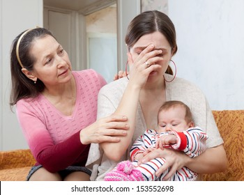 Mature woman comforts crying adult daughter with baby at home