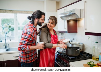 Mature woman is cooking in her kitchen and her son is looking over her shoulder to see what she is making.