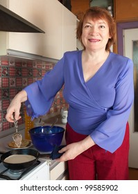 Mature woman cooking pancake at her kitchen