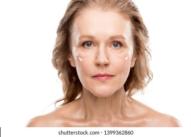 mature woman with cosmetic cream on face looking at camera Isolated On White
