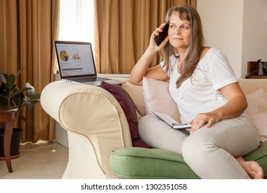 Mature woman is discussing business on the phone working from her apartment