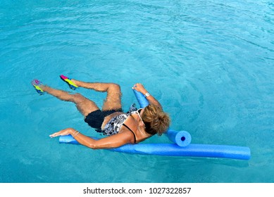 Mature Woman doing Auqua Aerobics with Pool Noodles in Outdoor Swimming Pool