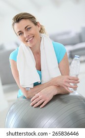 Mature woman doing fitness exercises at home