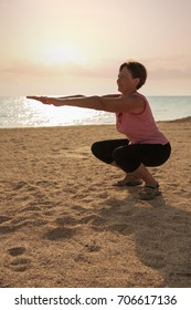 Mature woman doing gymnastic exersices at the sea beach in the morning