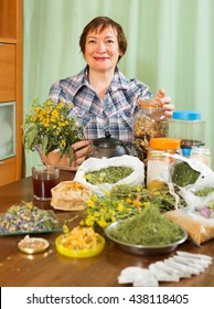 mature woman doing herbal tea with herbs and smiling at home