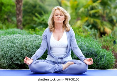mature woman doing lotus yoga position outside in the garden
