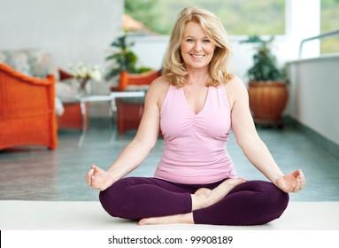 mature woman doing lotus yoga position on her home balcony