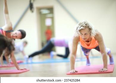 Mature woman doing push-up on padded mat