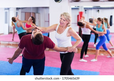 Mature woman is doing self-defence moves with trainer in sporty gym