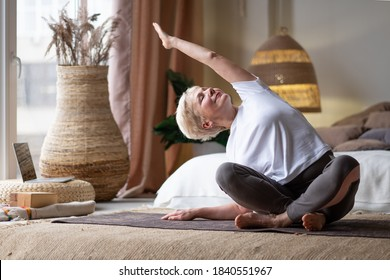 Mature Woman doing stretching yoga side bend at home.