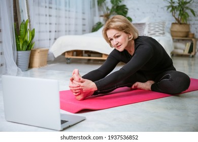 mature woman doing workout online on laptop
