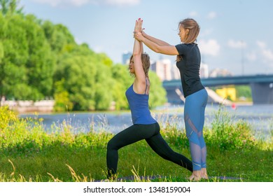 mature woman doing yoga outdoors with an individual trainer