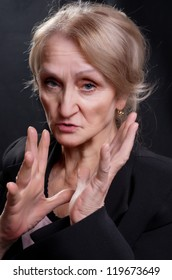 Mature woman dressed in suit gesticulate