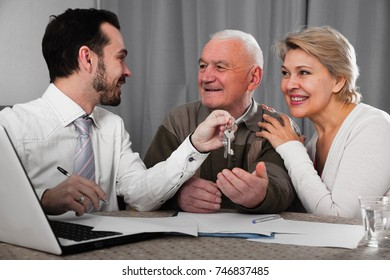 Mature woman and elderly man signing contract of rent apartments and hand over keys