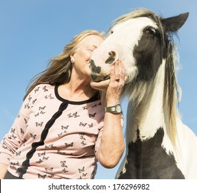mature woman embracing and kissing her horse